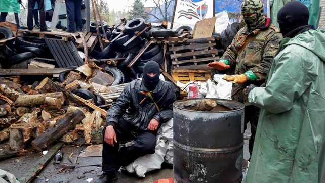 Pro-Russian protesters warm themselves around a fire in front of an occupied police station in Slaviansk