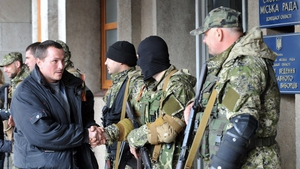 A Pro-Russia man shakes hand with armed men outside the regional administration building seized and guard by separatists in the eastern Ukrainian city of Slavyansk