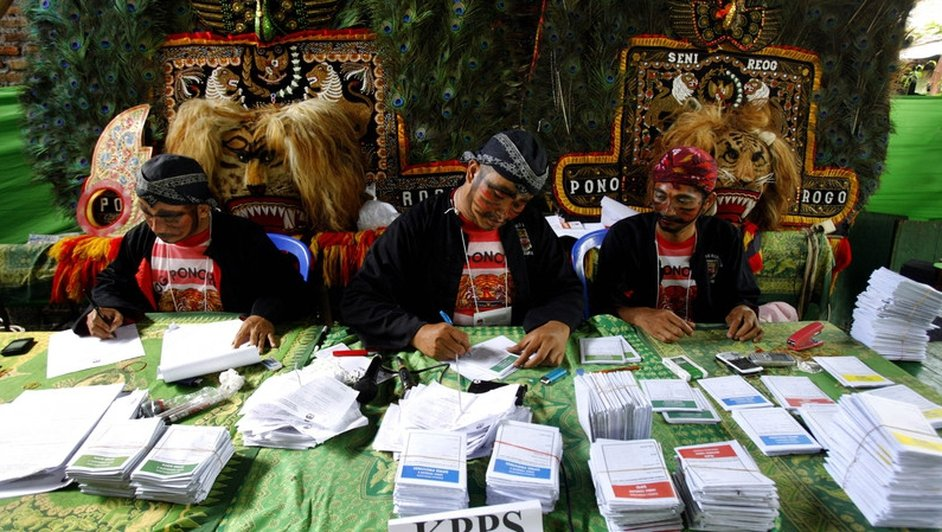 Electoral officials wear traditonal 'Reog Ponorogo' outfits at a polling station in Medan, Indonesia (Pic: EPA)
