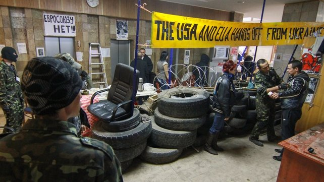 Pro-Russian protesters gather at a barricade of tyres inside the occupied regional administration building in Donetsk
