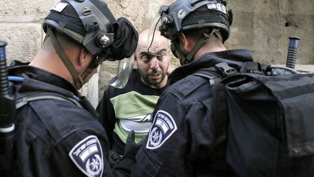 Israeli riot police check the ID as they arrest a Palestinian inside the Al Aqsa Mosque on Monday
