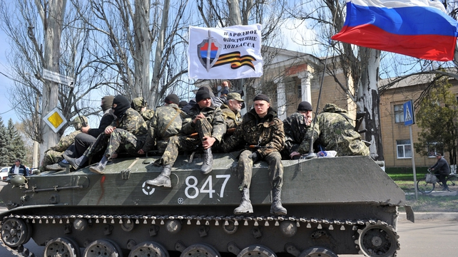 Men wearing military fatigues ride on an armoured personnel carrier in the eastern Ukrainian city of Slaviansk