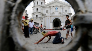 A Filipino man is whipped on his back in front of a church on Holy Thursday in San Fernando city