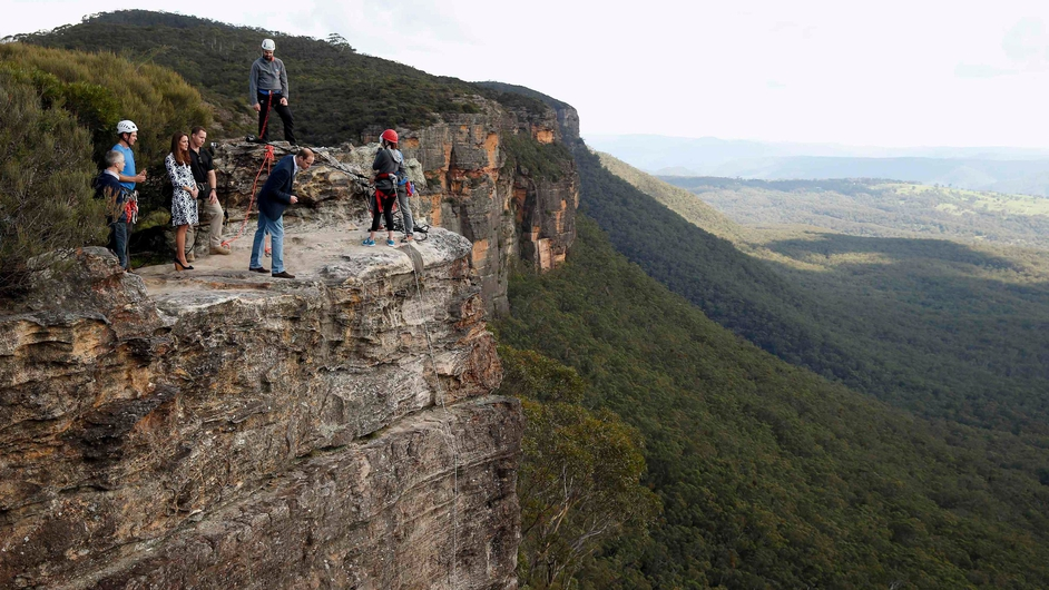 Britain's Prince William leans over a cliff as he visits the Blue Mountains in Katoomba in Australia