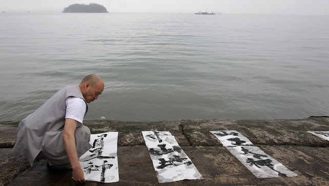 A monk performs a Buddhist ceremony for missing passengers of the sunken ferry at Jindo port