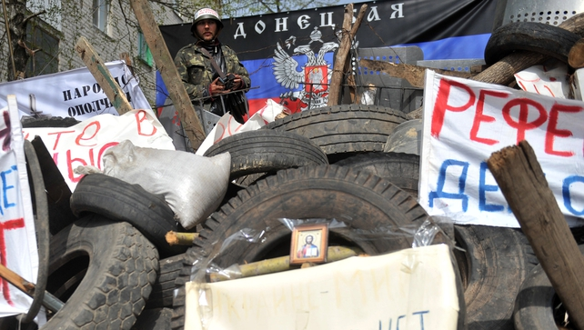 A pro-Russia activist stands guard in front of a flag of the so-called Donetsk republic