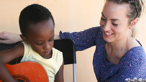 Kathryn Thomas looks on as a young Rwandan learns their guitar chords