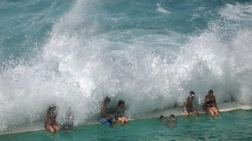 Waves break over people as they sit in an ocean pool at Sydney's famous Bondi Beach on Good Friday in Sydney