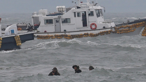 Divers fight against high waves as they struggle to search for hundreds of missing passengers
