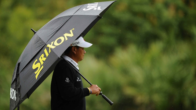 Leader KJ Choi shields himself from the rain in South Carolina