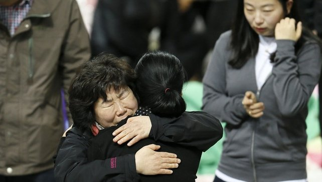 Family members of missing passengers hug each other as they wait for news about their missing relatives