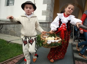 Children carry a basket containing food during the traditional blessing of Easter meals in the village of Bialy Dunajec, Poland.