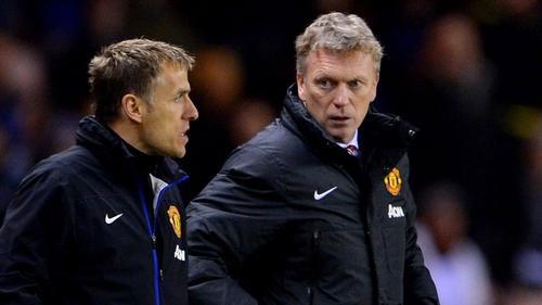 Manchester United coach Phil Neville (L) with manager David Moyes
