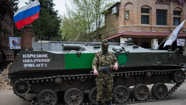 An armed pro-Russian protester stands in front of an occupied police station in Slaviansk, Ukraine