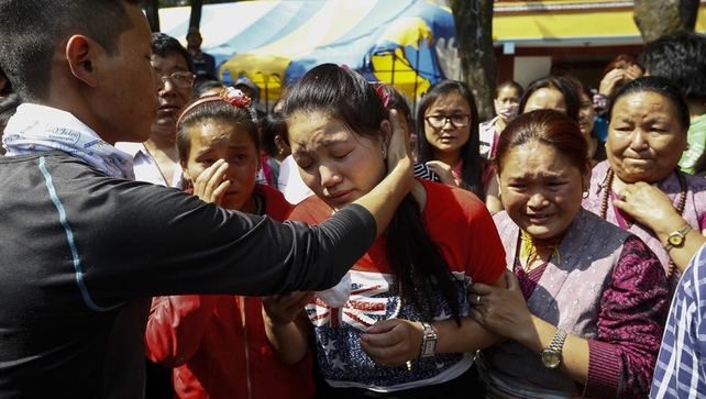 The daughter of one of the victims of the avalanche is comforted by friends