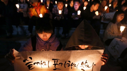 People hold candles as they pray for the safe return of passengers of the sunken ferry in Ansan, South Korea