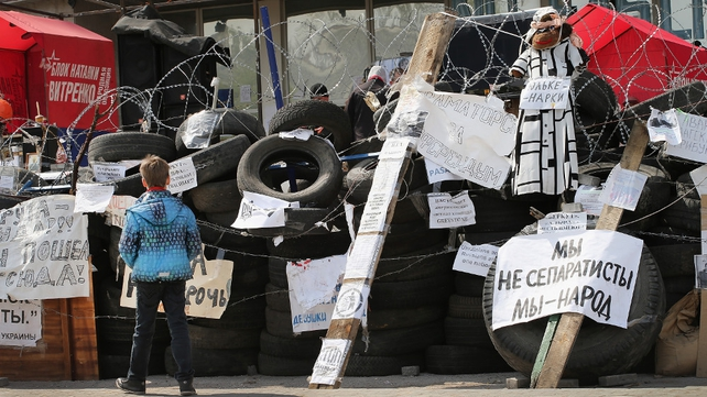 A young boy reads propaganda attached to a barricade in Donetsk, Ukraine