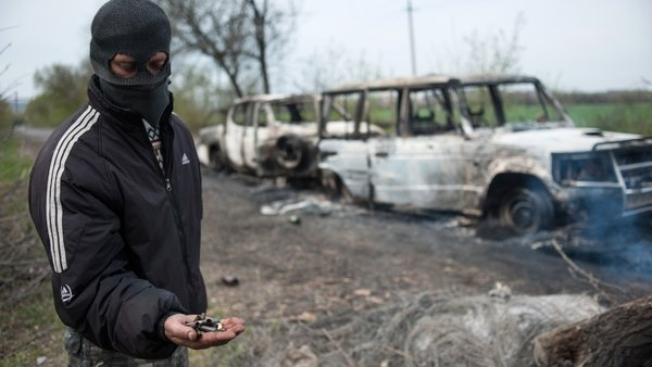 An activist shows ammunition near burned out vehicles in front of a pro-Russian blockade near Slaviansk