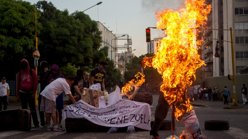 A figure with the image of President Nicolas Maduro is burned during the tradition of the Burning of Judas in Caracas, Venezuela
