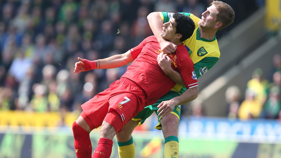 Norwich City's Michael Turner has a tight grip on Liverpool's Luis Suarez during a Premier League clash at Carrow Road