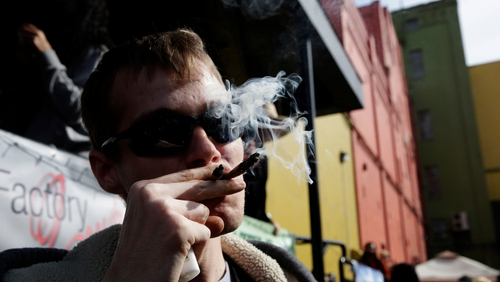 Anthony Nitowski smokes two joints outside at Hempfest in Seattle, Washington