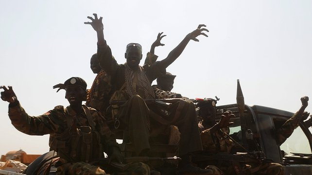 Members of South Sudan's former rebel army the Sudan People's Liberation Army (SPLA) cheer after capturing the key north oil city of Bentiu from rebels on January 12, 2014