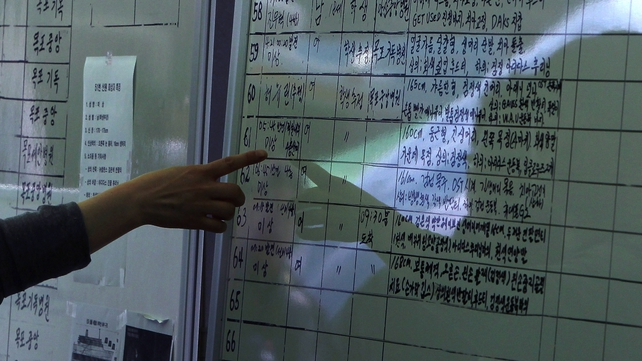 A relative checks lists of dead of the sunken ferry at Jindo port