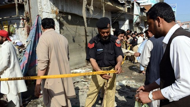 Pakistani security officials inspect the site of a bomb blast in Charsadda