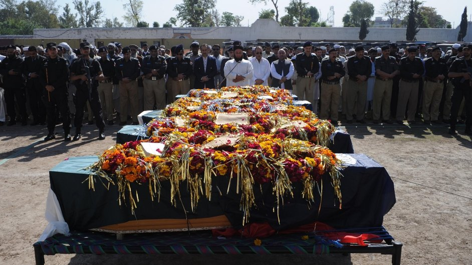 Pakistani police officials offer funeral prayers for their colleagues who were killed in an overnight ambush in Peshawar