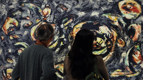 Visitors look at an authentic untitled work by US artist Jackson Pollock belonging to the Guggenheim foundation