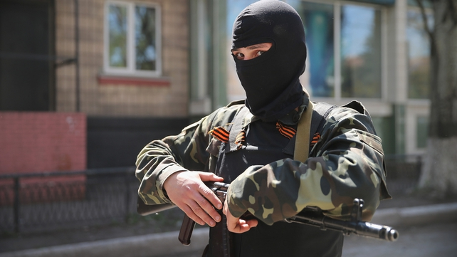 A pro-Russian militant stands guard in front of the occupied Ukraine Security Service building in Slaviansk