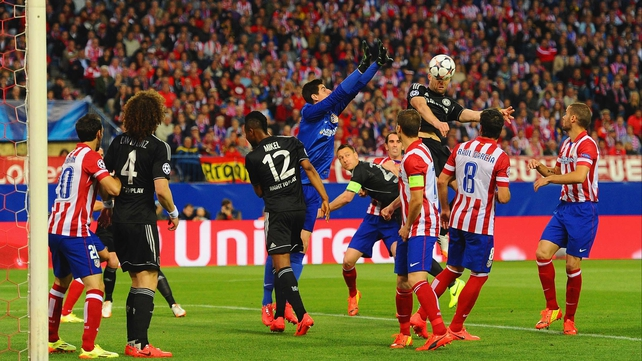 Gary Cahill gets to a cross ahead of Atletico 'keeper Thibaut Courtois