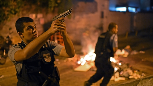 A Brazilian police special forces member takes position during a violent protest in a favela near Copacabana in Rio de Janeiro