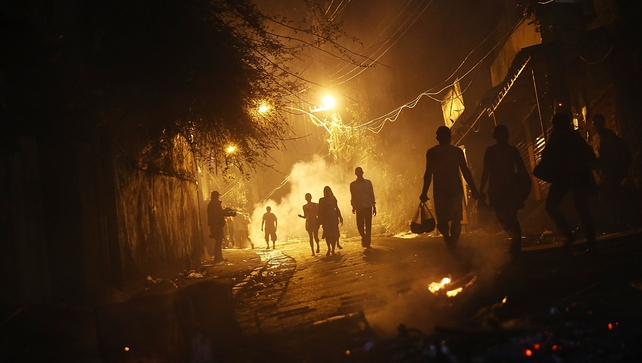 Residents walk past fires set by protesters following shootings in a community near Copacabana Beach
