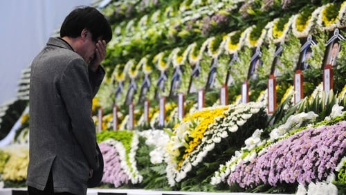 A mourner pays tribute to the victims at an altar set up at Ansan Olympic Memorial Hall