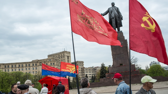 A small group of pro-Russians gather below a statue of Vladimir Lenin in Kharkiv, Ukraine