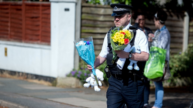 A police officer carries some floral tributes to the scene in New Malden