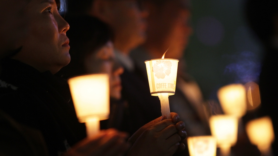 People hold candles at a memorial altar for the victims of the South Korean ferry disaster
