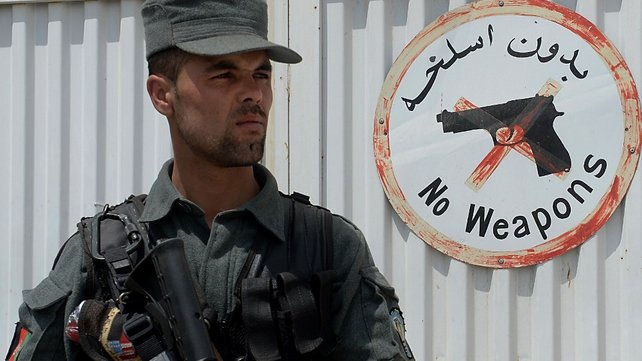 An Afghan policeman keeps watch outside the Cure hospital in Kabul