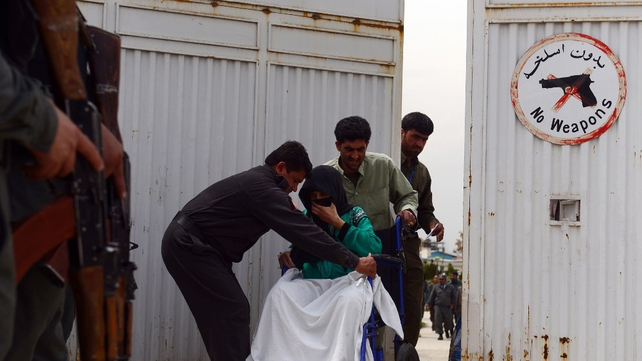 hospital attendants help a patient at the gate of the Cure Hospital