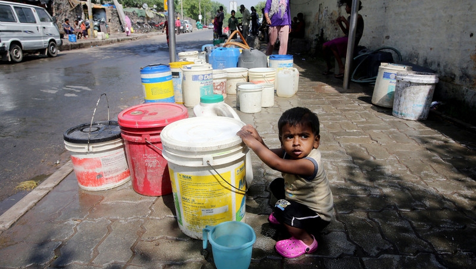 An Indian child plays around with buckets filled with water from a water tanker sent by civil authorities to ensure they get their daily supply of water in New Delhi, India.