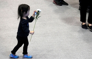 A child walks to pay tribute to victims, who were killed in the ferry Sewol's sinking, at a joint incense-burning altar set up at Ansan Olympic Memorial Hall in Ansan, south of Seoul.