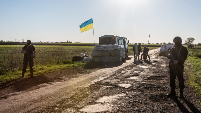 Ukrainian military personnel guard a check point near the town of Barvinkova