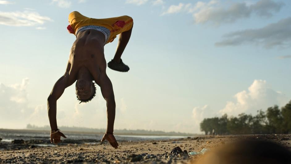 A man streches on a beach in Dar es Salaam, Tanzania