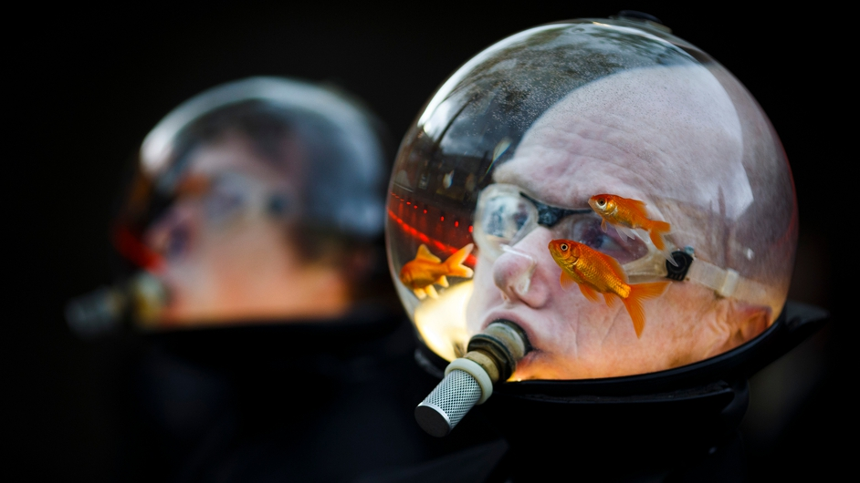 A man wearing a water jar filled with live fish over his head welcomes spectators for the opening ceremony of the 20th edition of the international film festival 'Visions du Reel' in Nyon, Switzerland