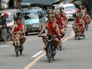 Filipino Ifugao tribesmen ride on wooden scooters during the Imbayah Festival in the upland town of Banaue, Ifugao province, Philippines