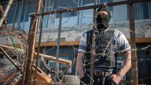 A masked pro-Russian protestor stands behind a barb wire crowned barricade near the occupied regional administration building in Donetsk, Ukraine