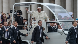 Pope Francis stands on the popemobile surrounded by bodyguards as he waves to pilgrims in St Peter's Square