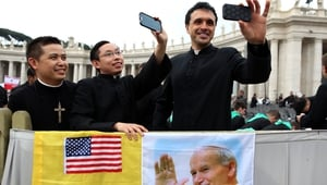 Priests gathered in St Peter's Square take selfies