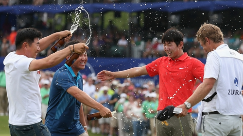 Seung-Yul Noh celebrates with golfers Charlie Wi and YE Yang and his caddy Scott Saitinac after his win